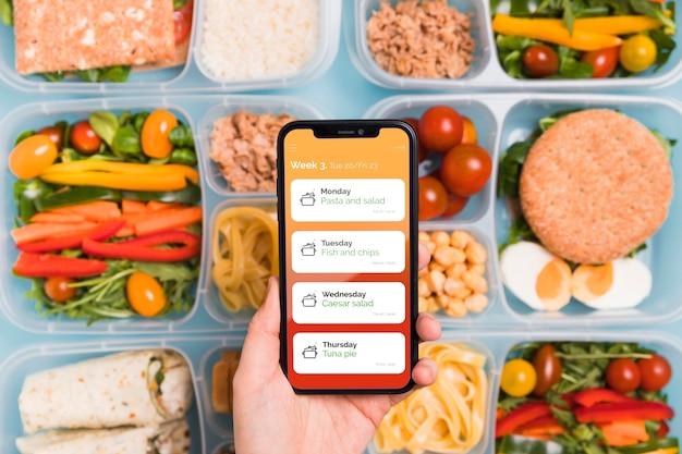 Vista superiore dello smartphone della tenuta della mano con i pasti previsti