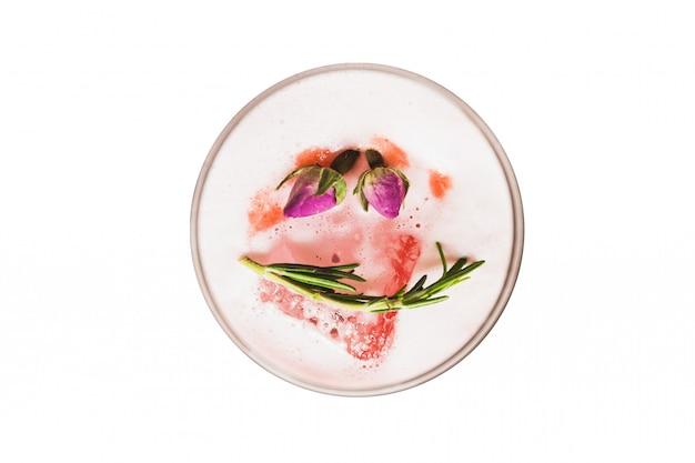 Vista superiore isolata del cocktail rosso nella guarnizione di vetro di vino con schiuma, fiori e rosmarino.