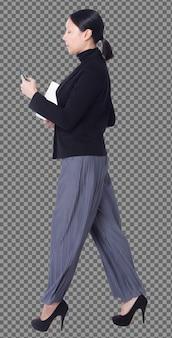Volledige lengte figuur van 40s 50s aziatische lgbtqia+ vrouw zwart haar pak broek en schoenen, wandelende telefoon. vrouw maakt gebruik van slimme telefoon, notebook en loop links rechts check over witte achtergrond geïsoleerd