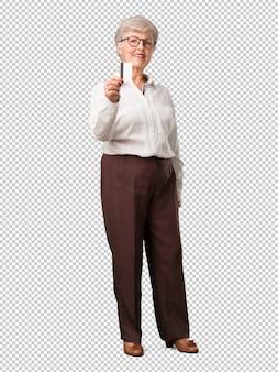 Volledige lichaams hogere vrolijke vrouw en glimlachend, zeer enthousiast houdend de nieuwe bankkaart