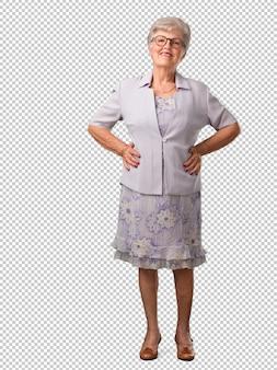 Volledige lichaams hogere vrouw met handen op heupen, status, ontspannen en glimlachend, zeer positief en vrolijk