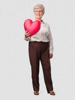 Volledige lichaams hogere vrouw vrolijk en zeker, aanbiedend een hartvorm naar de voorzijde, concept liefde, gezelschap en vriendschap