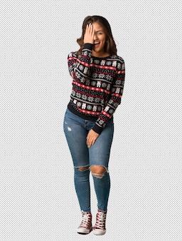 Volledige lichaams jonge vrouw die het gelukkige en bedekken van kerstmis van kerstmis jersey schreeuwen gezicht met hand draagt