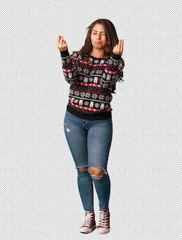 Volledige lichaams jonge vrouw die kerstmis jersey draagt die een gebaar van behoefte doet