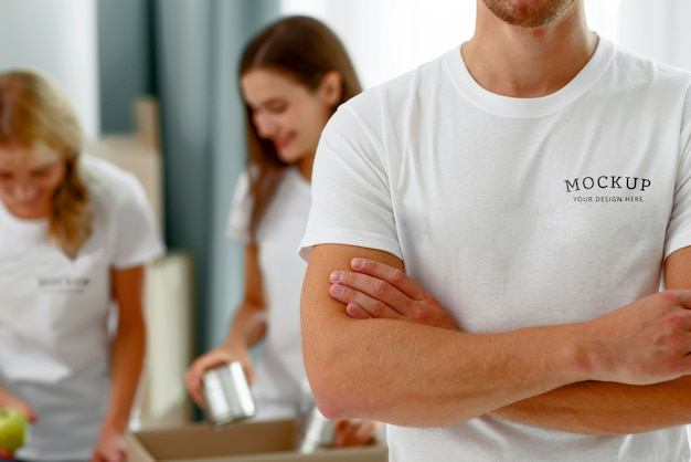 Voluntario masculino posando con los brazos cruzados mientras sus colegas preparan cajas de donación con comida