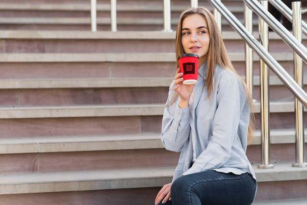 Vooraanzicht moderne blonde meisje met een kopje koffie mock-up