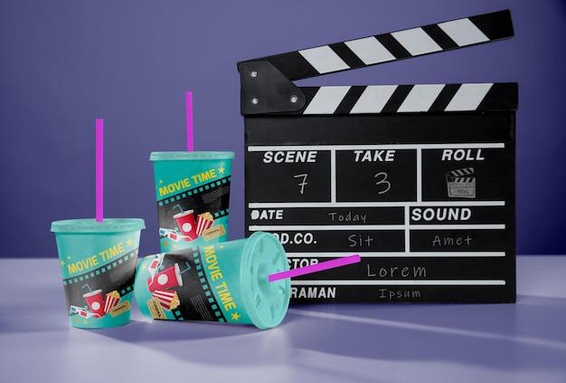 Vooraanzicht van drie bioscoop bekers met rietjes en filmklapper