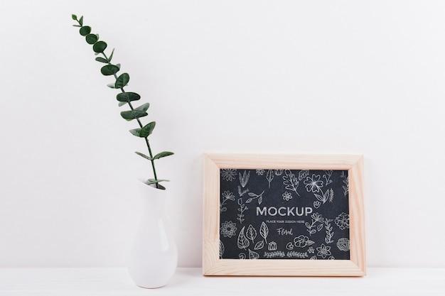 Vooraanzicht van frame mock-up met vaas en plant