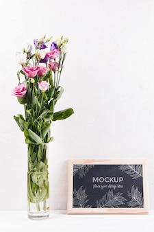 Vooraanzicht van frame mock-up met vaas met bloemen