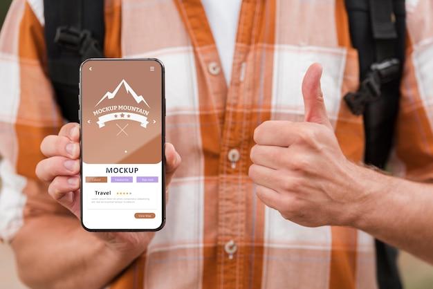 Vooraanzicht van smiley man met smartphone en duimen opgevend tijdens het kamperen
