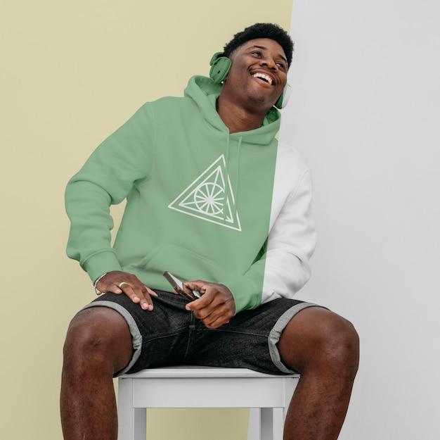 Vooraanzicht van stijlvolle man in hoodie met koptelefoon