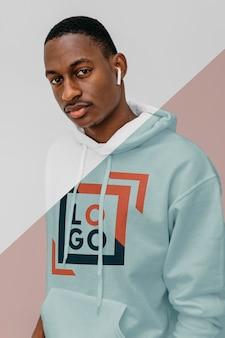 Vooraanzicht van stijlvolle man in hoodie met oordopjes
