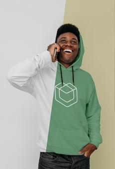 Vooraanzicht van stijlvolle man in hoodie met smartphone