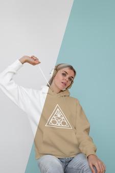 Vooraanzicht van stijlvolle vrouw in hoodie met koptelefoon