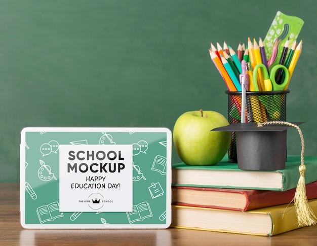 Vooraanzicht van tablet met schoolbenodigdheden voor onderwijsdag