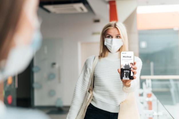 Vooraanzicht van vrouw die met medisch masker telefoon steunt