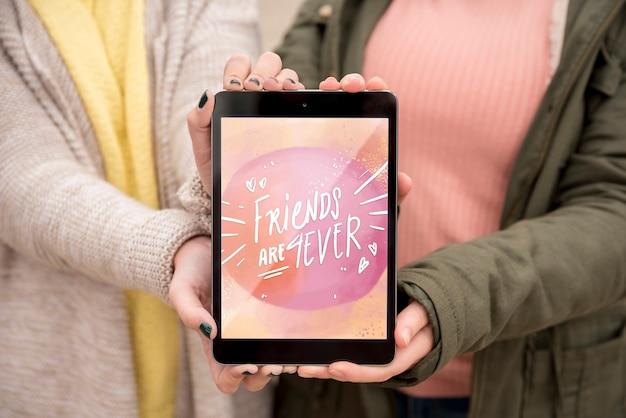 Vriend die de gelukkige tablet van de vriendschapsdag houden