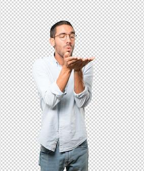 Vriendelijke jonge man die een gebaar maakt om een kus met zijn hand te sturen