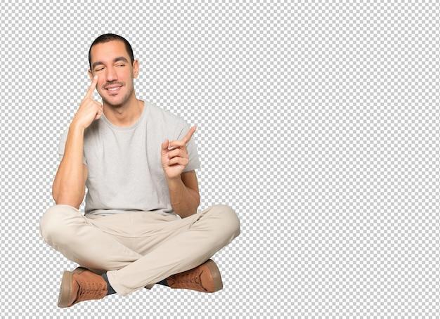 Vriendelijke jonge man die een gebaar maakt om voorzichtig te zijn met zijn hand die naar zijn oog wijst
