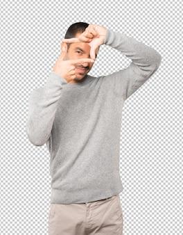Vriendelijke jonge man die een gebaar maakt van het nemen van een foto met de handen