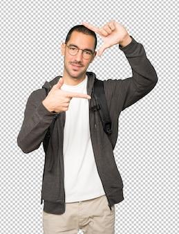 Vriendelijke student die een gebaar maakt om een foto met de handen te nemen