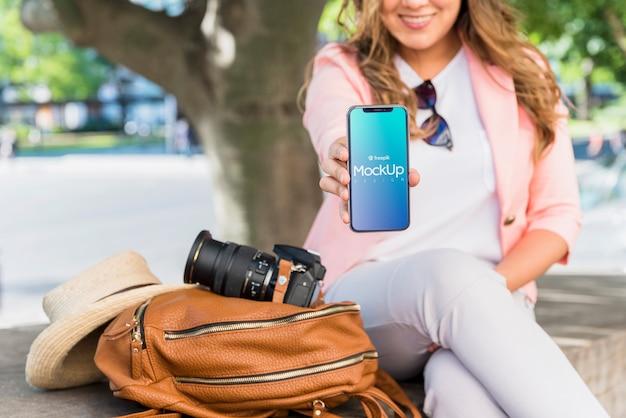 Vriendelijke vrouw die smartphonemodel voorstelt