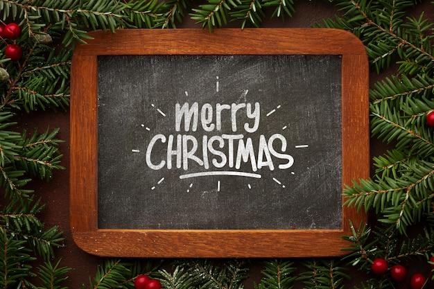 Vrolijk kerstfeest op schoolbord en pijnboombladeren