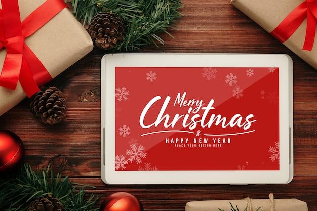 Vrolijk kerstfeest tabletcomputer mockup met decoraties van dennenbladeren