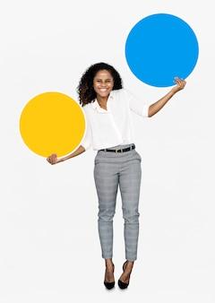 Vrolijke vrouw die kleurrijke ronde raad houdt