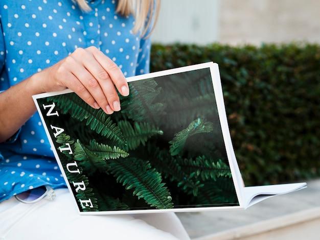Vrouw buiten lezen magazine