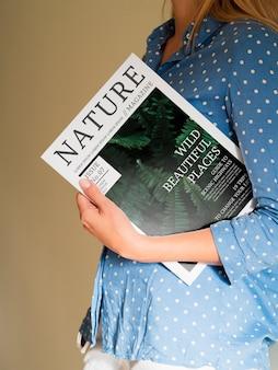 Vrouw die een aardmagazine dicht bij haar borst houdt