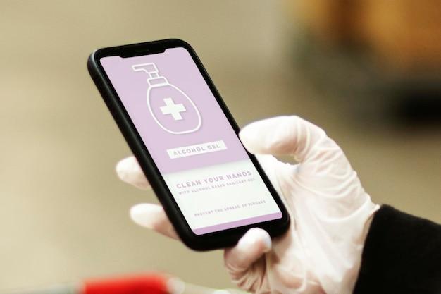 Vrouw die een latexhandschoen draagt tijdens het gebruik van een mobiele telefoon om het mockupscherm van coronavirusbesmetting te voorkomen
