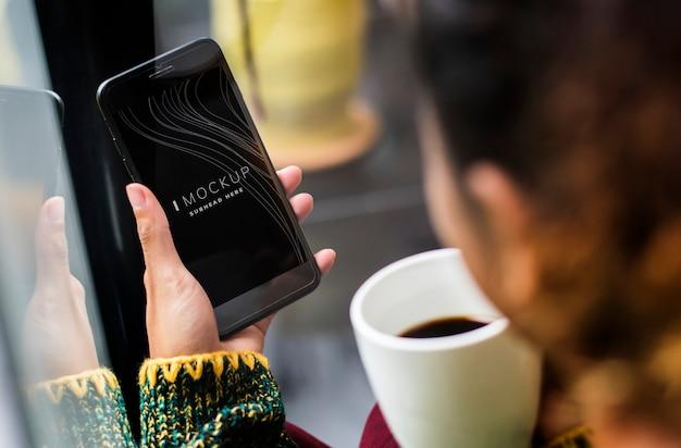 Vrouw die een mobiel telefoonmodel in een koffiewinkel gebruikt