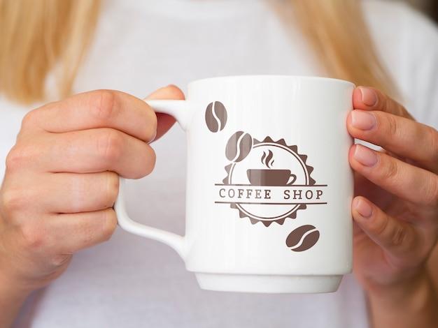 Vrouw die een model van de koffiemok steunt