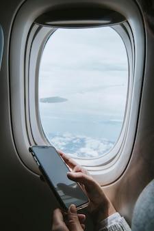 Vrouw die een smartphone gebruikt in een vliegtuig