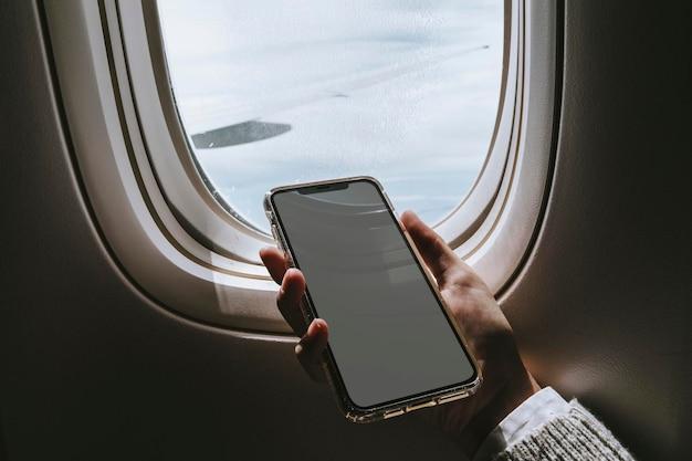 Vrouw die een smartphone in een vliegtuig gebruikt