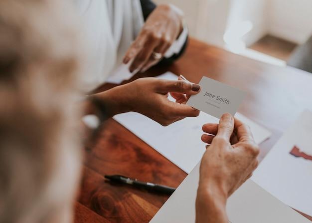 Vrouw die een visitekaartjemodel overhandigt