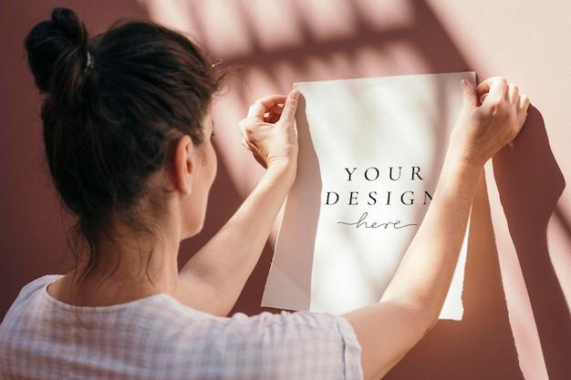 Vrouw die een wit postermodel vastmaakt aan een pastelroze muur
