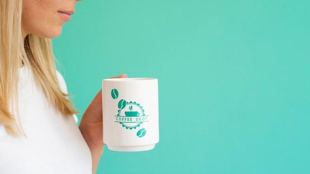 Vrouw die een witte koffiemok met exemplaarruimte steunt