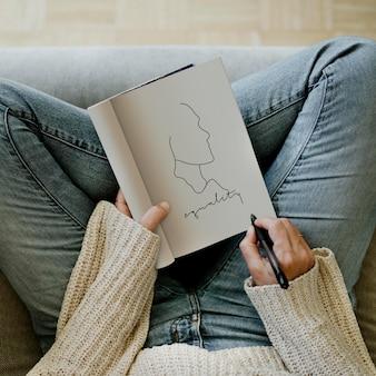 Vrouw die gelijkheid schrijft in het ontwerp van een notitieboekjemodel