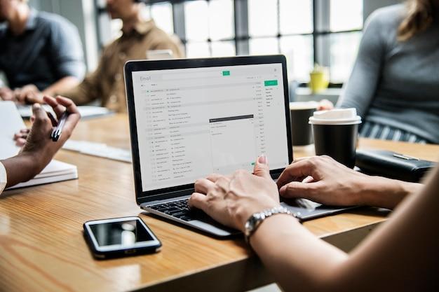 Vrouw die haar e-mail in een vergadering controleert