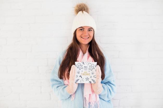 Vrouw die het vierkante model van de kerstmiskaart houdt