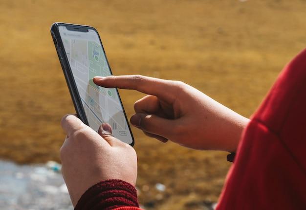 Vrouw die in openlucht een toepassing van de smartphonekaart gebruiken