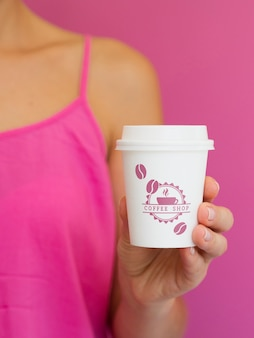 Vrouw die klein document koffiekopmodel houdt