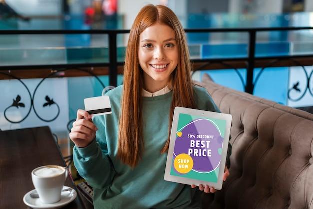 Vrouw die met een creditcard en een tablet in haar handen glimlacht