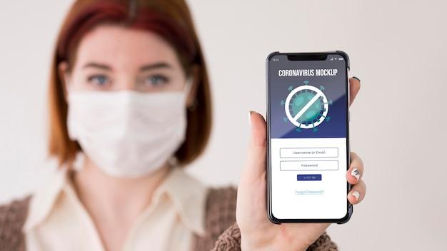 Vrouw die met maskers smartphone houdt