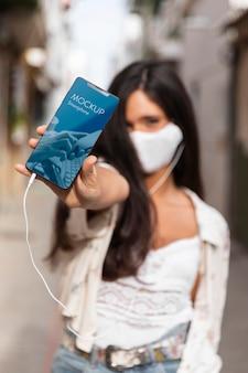 Vrouw die met medisch masker aan muziek op oortelefoons luistert