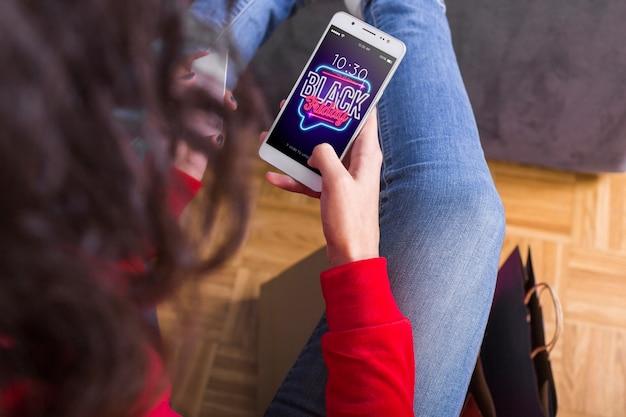 Vrouw die naar zwarte vrijdag op smartphone zoekt