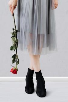 Vrouw die op haar tenen staat en een rode roos vasthoudt