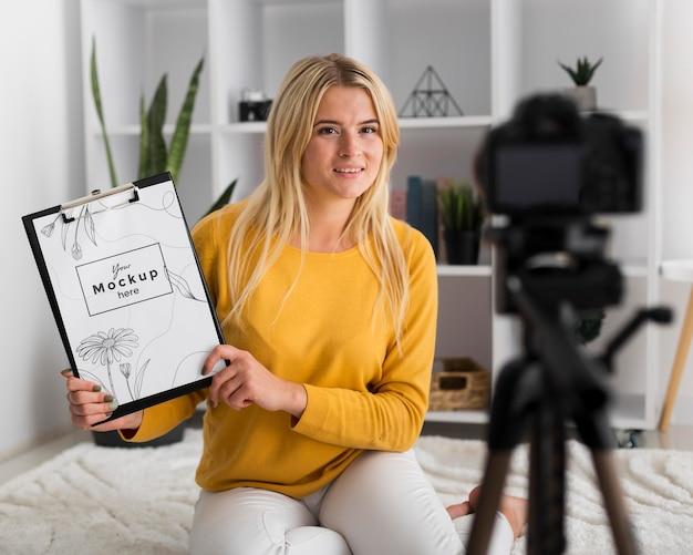Vrouw die thuis klembordmodel toont